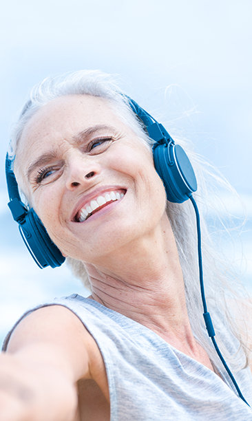 Woman in tank top with ear phones stretching her arm out. She is by the sea.